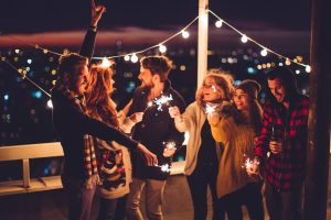 Couple of friends having a party on the rooftop of the building at sunset. Drinking bottles of beer and holding sparklers.. Wearing knitted sweaters, hats and scarfs. They are happy and joyful.