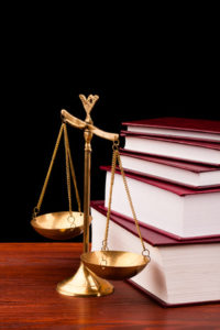 books of justice and scale on wooden table